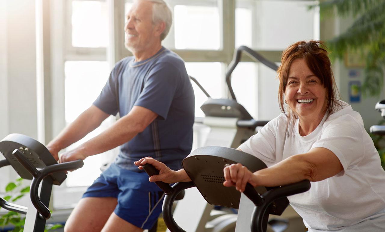 Couple qui fait du vélo d'appartement – Ain Sport Santé