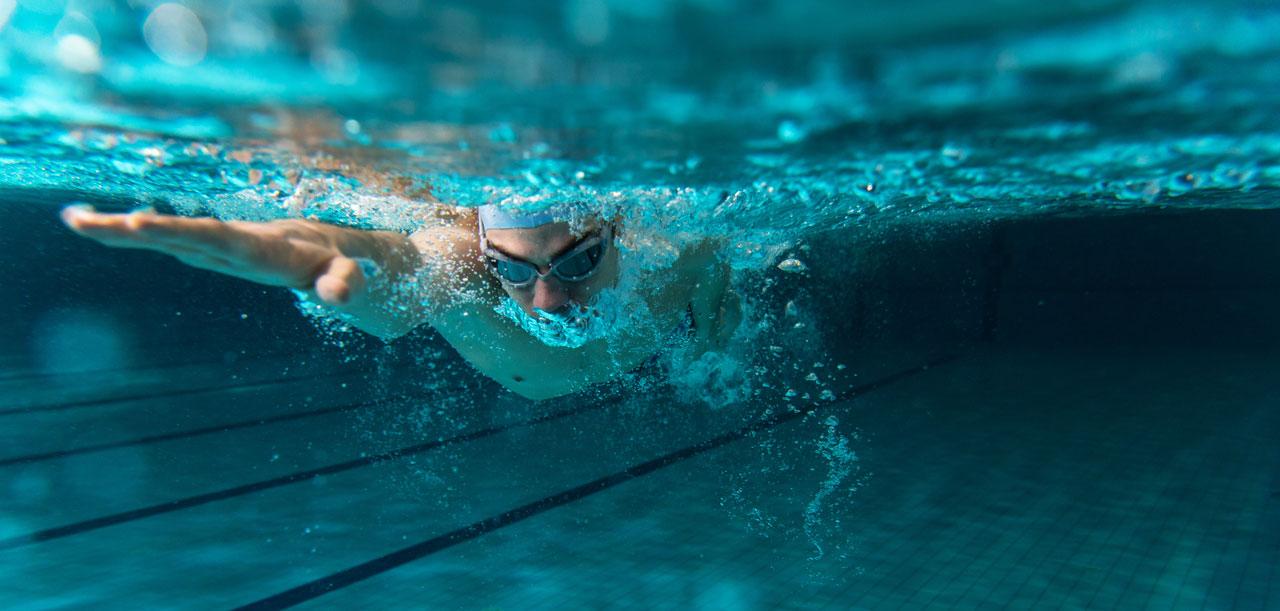 Nageur nageant le crawl dans une piscine – Ain Sport Santé